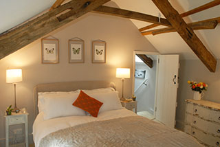 The bedroom with exposed wood beams in the restored cottage
