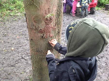 A child makes a clay model attached to a tree