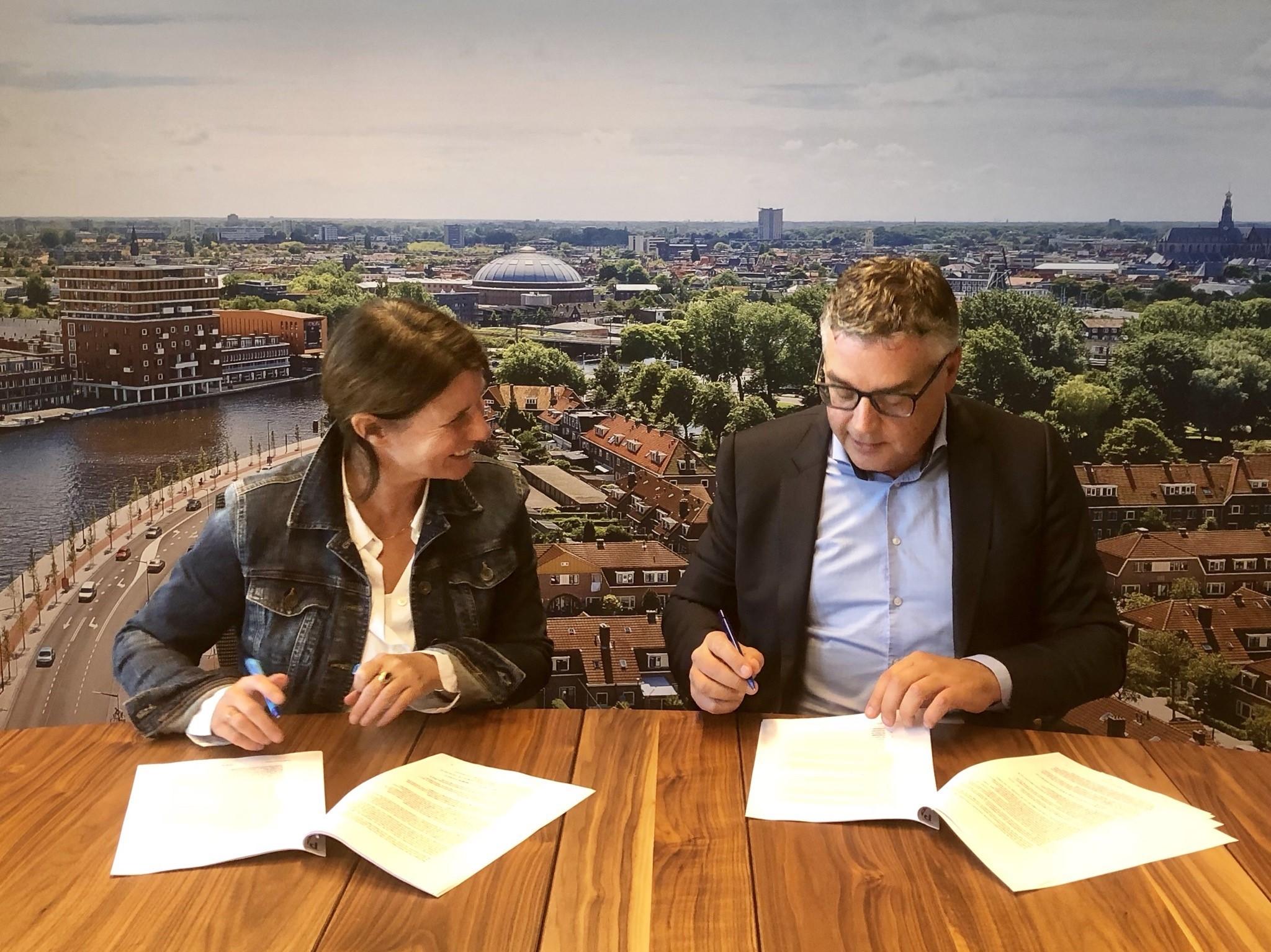 ré Wonen bestuurder Anke Huntjes en KBM-directeur Dick van der Plas zetten handtekening over project Staalstraat/De Bazellaan