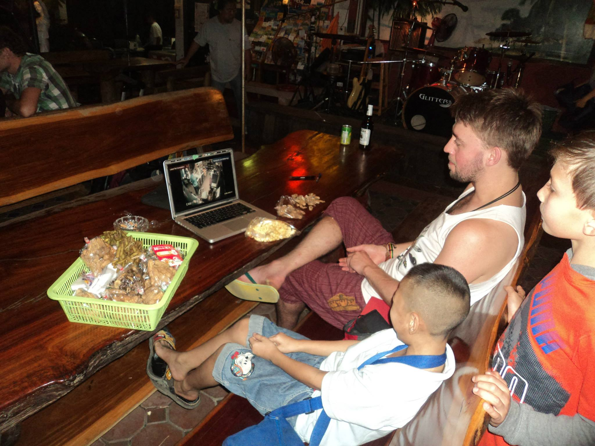 Mike Neumegen and two boys watching a laptop on a table with food
