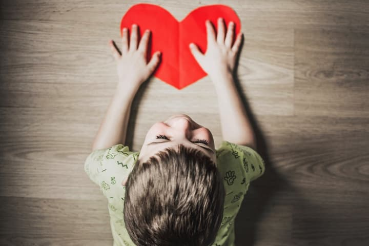 Child touching a paper heart