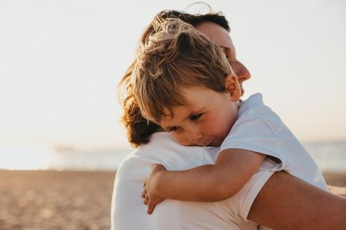 little-boy-in-white-shirt-cuddling-mother-over-shoulder-smiling
