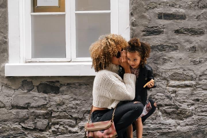 Mum whispering into her daughter's ear