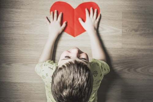 little-boy-on-ground-with-red-paper-heart-happy