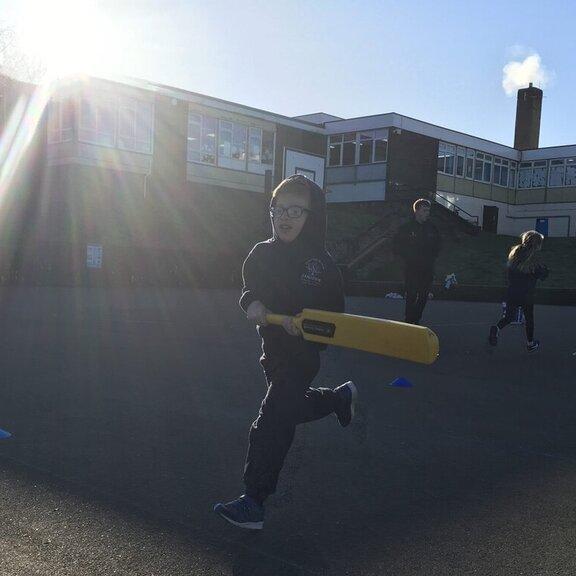 Boy in the playground running with cricket bat