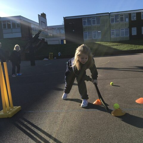 Girl practicing a cricket shot with a blue bat