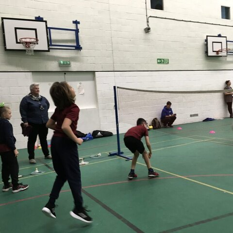 Pupils getting ready to return the shuttle cock in a game of badminton