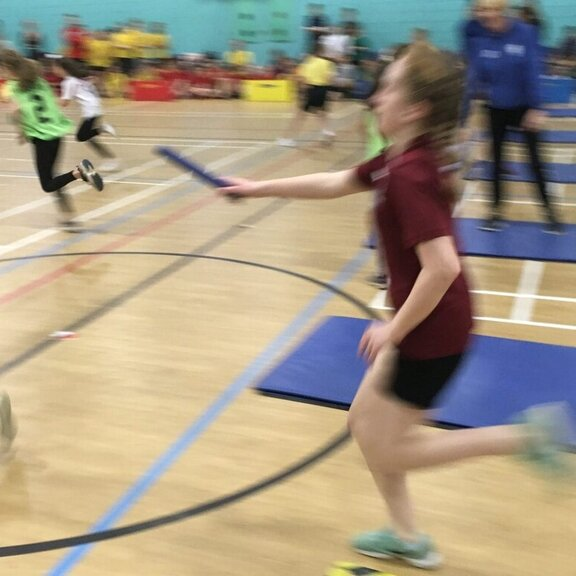 Two children passing the baton in a relay race