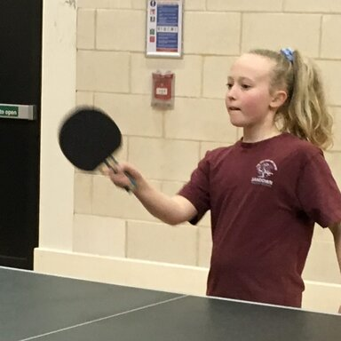 Girl concentrating on her table tennis shot