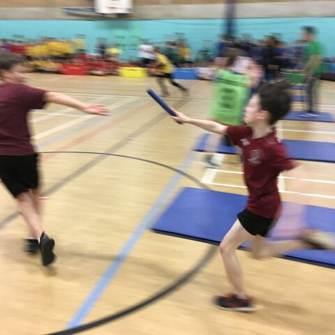 Two boys passing the baton in a relay race