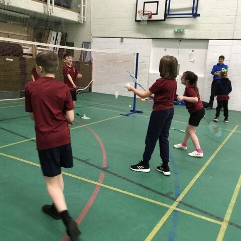 Coach watching the children play badminton