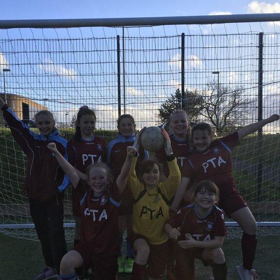 Girls football team posing in the goal