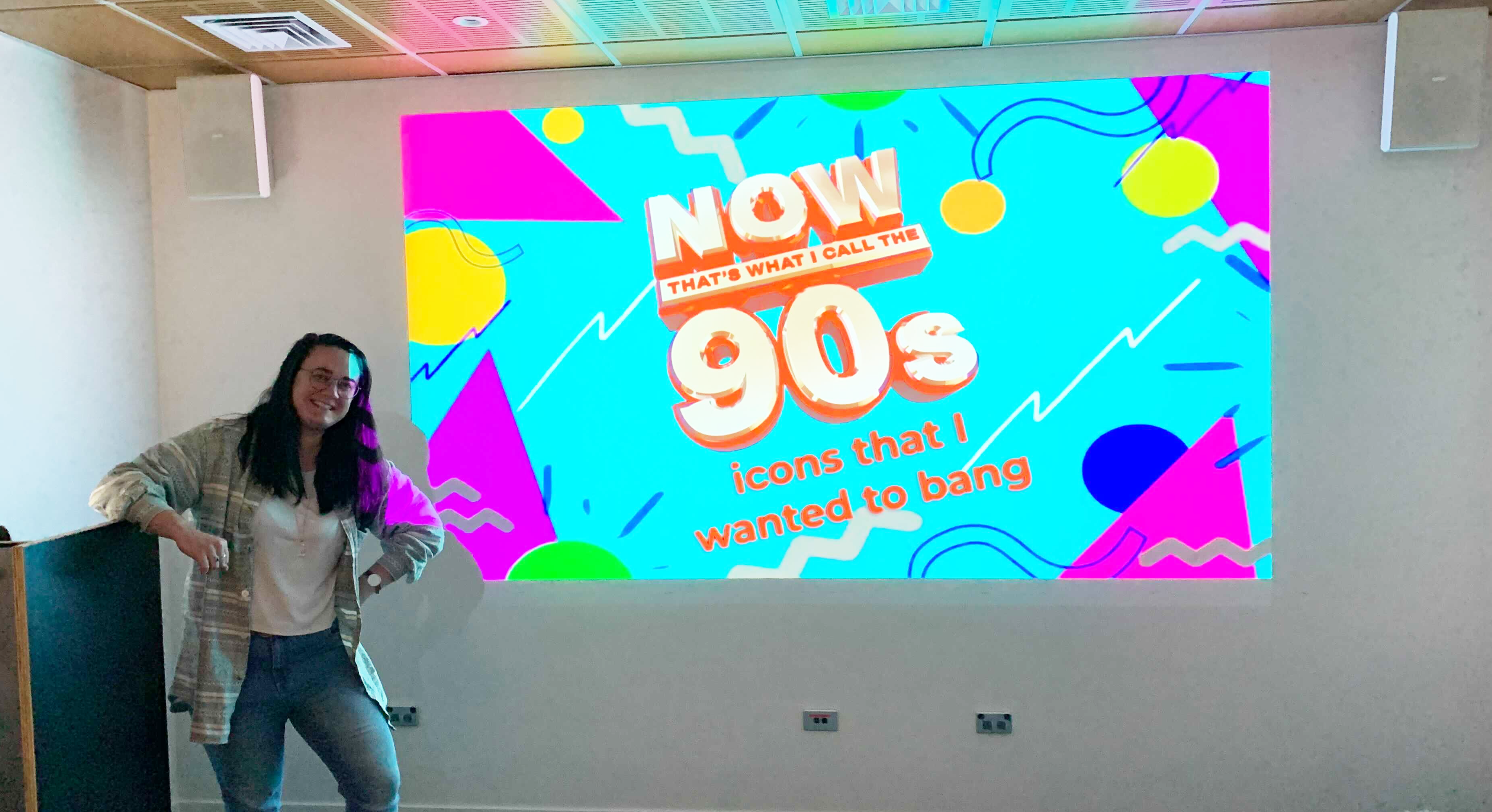 Chloe standing in front of a PowerPoint presentation about 90s icons