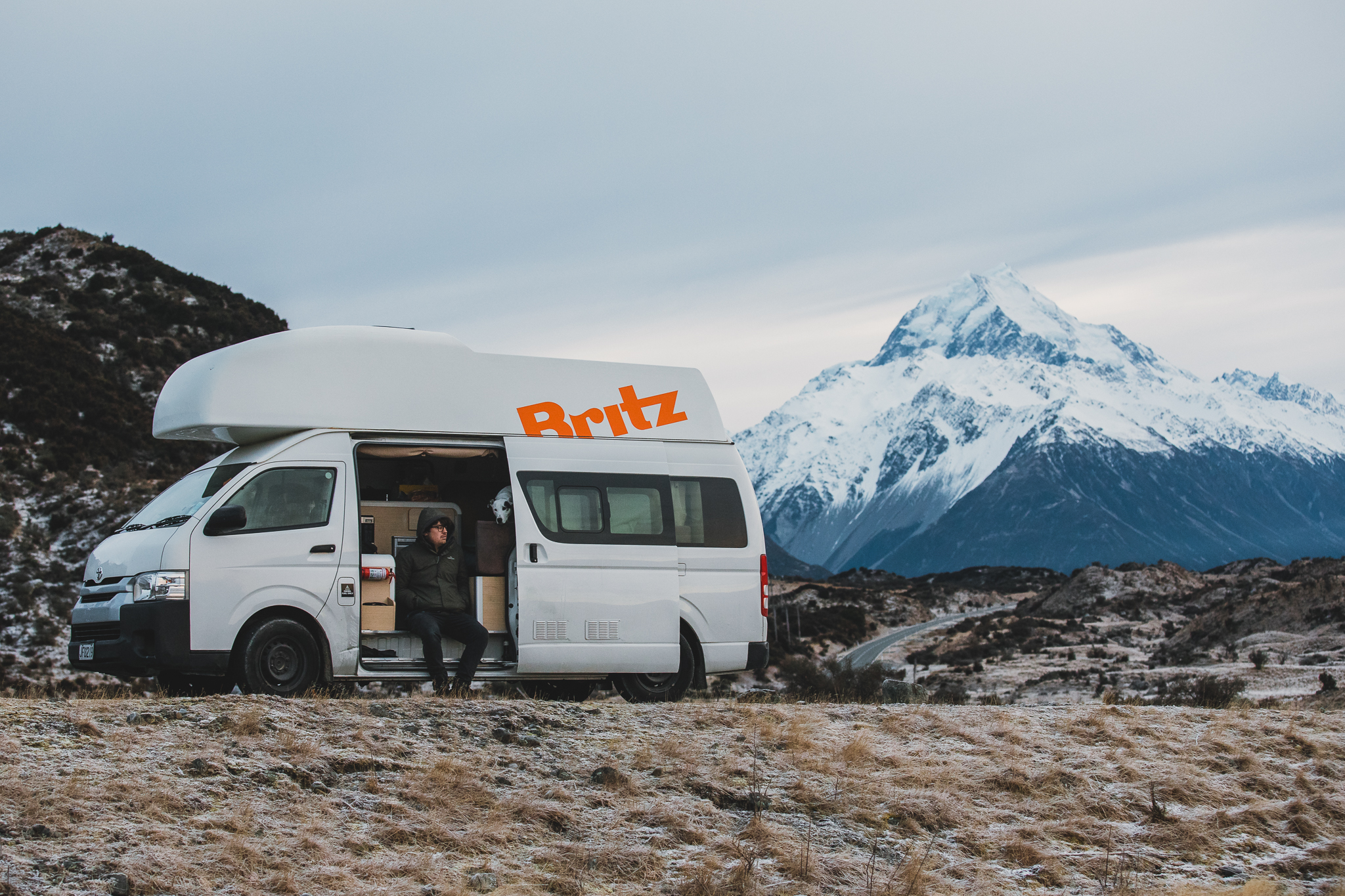 A man on a roadtrip holiday sits in a campervan in front of a mountain