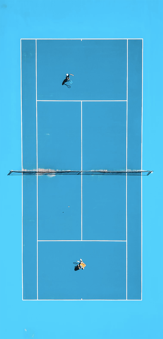 Bird's-eye view of tennis game on blue clay