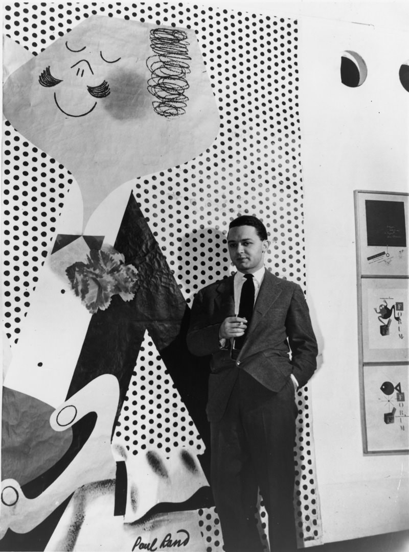 Paul Rand standing by one of his poster designs