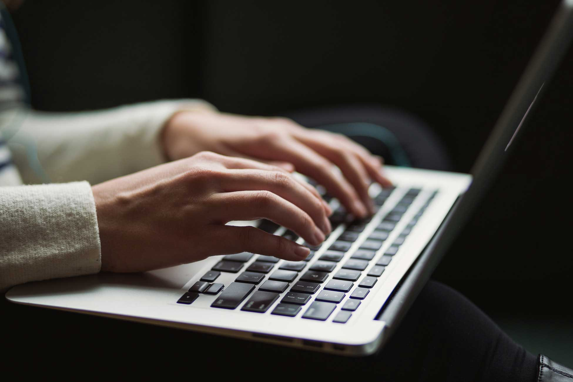Photo of a woman's hands typing on a laptop.