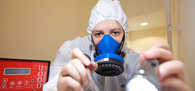 Asbestos analyst completing a visual inspection using a torch. Red air testing pump in the background.