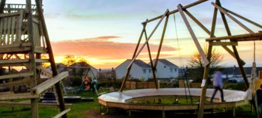Children playing at Gwealan Tops Adventure Playground with a sunset.