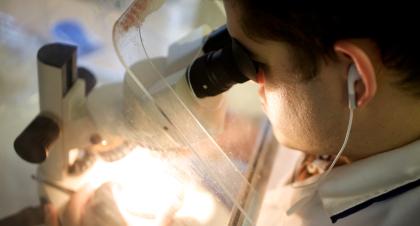 Asbestos analyst looking into microscope