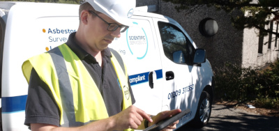 Asbestos consultant with tablet and van