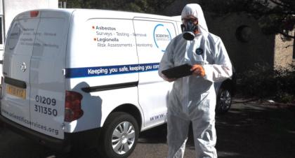 Asbestos surveyor in PPE by van