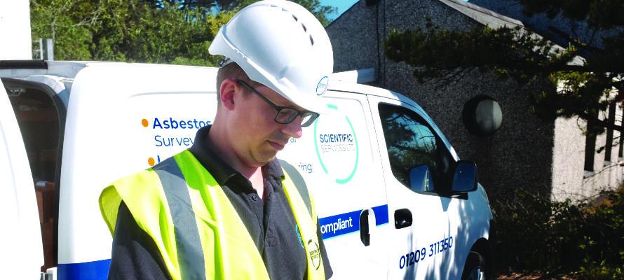 Asbestos surveyor looking at a tablet by a van.