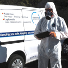 Asbestos consultant looking at a tablet with a van