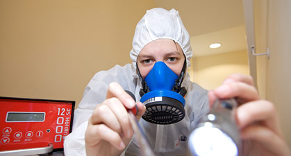 Asbestos analyst with pump and PPE