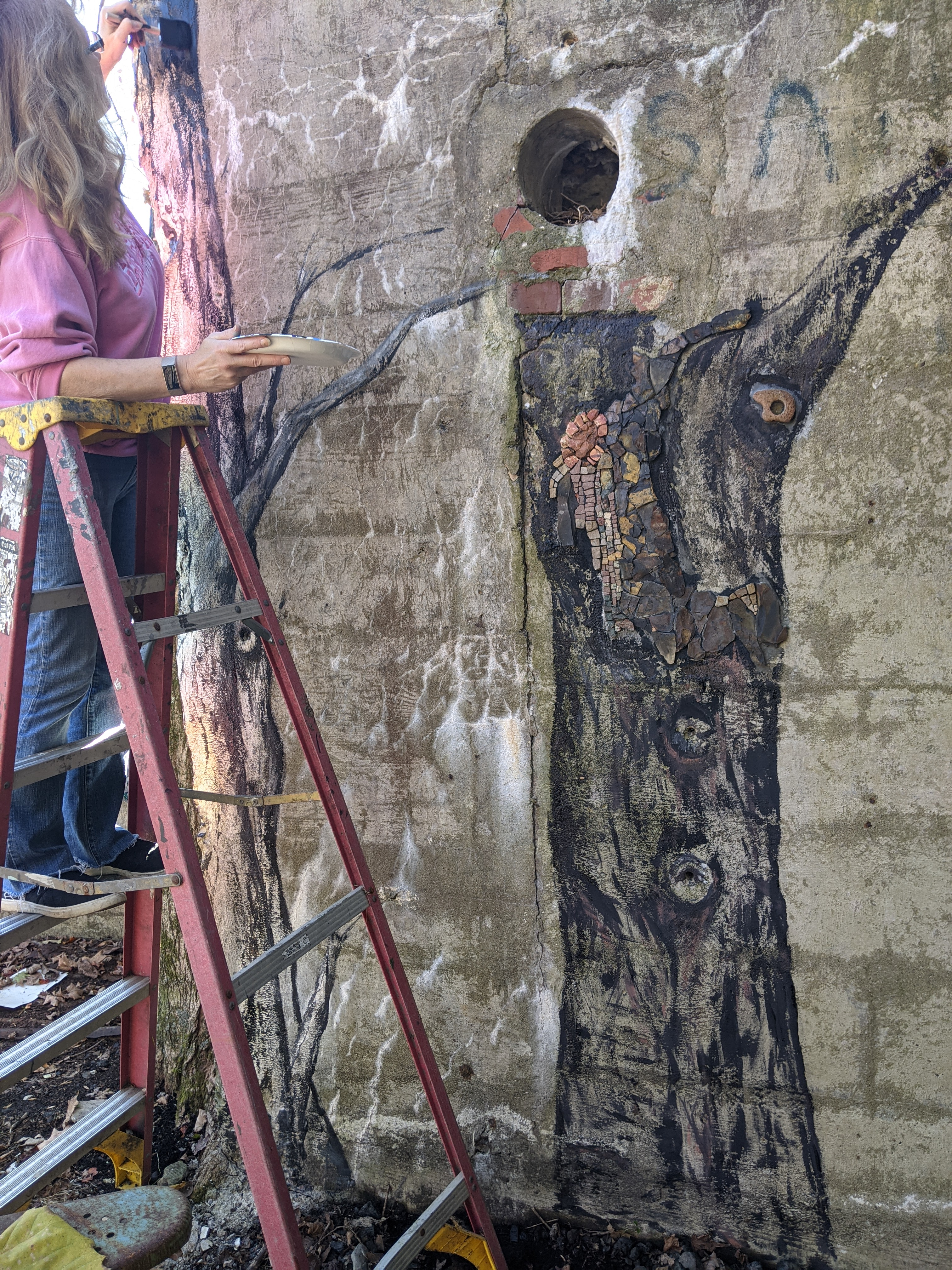 Local artist, Jan Dongilli, painting the tree for the birds of The Feather Project
