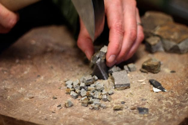chopping stone with hammer and hardie for mosaic