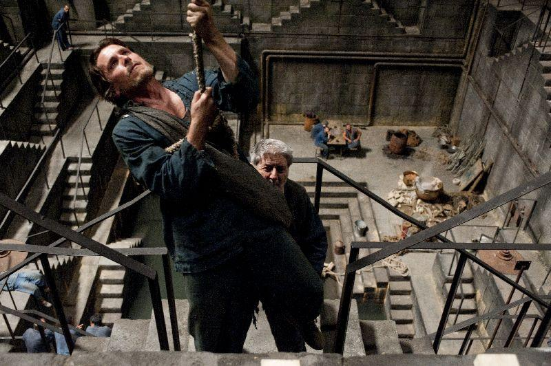 Bruce Wayne, played by Christian Bale, trying to escape the prison he's been put in by Bane in the Dark Knight Rises.