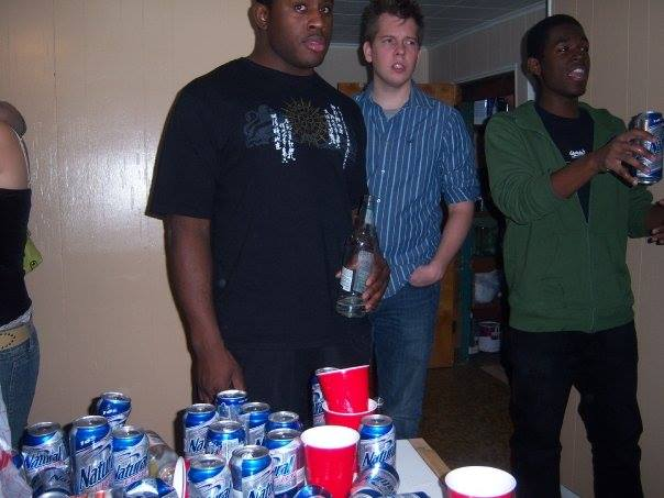 Photo of Ed Latimore holding a beer at a house party, looking pretty unhappy.