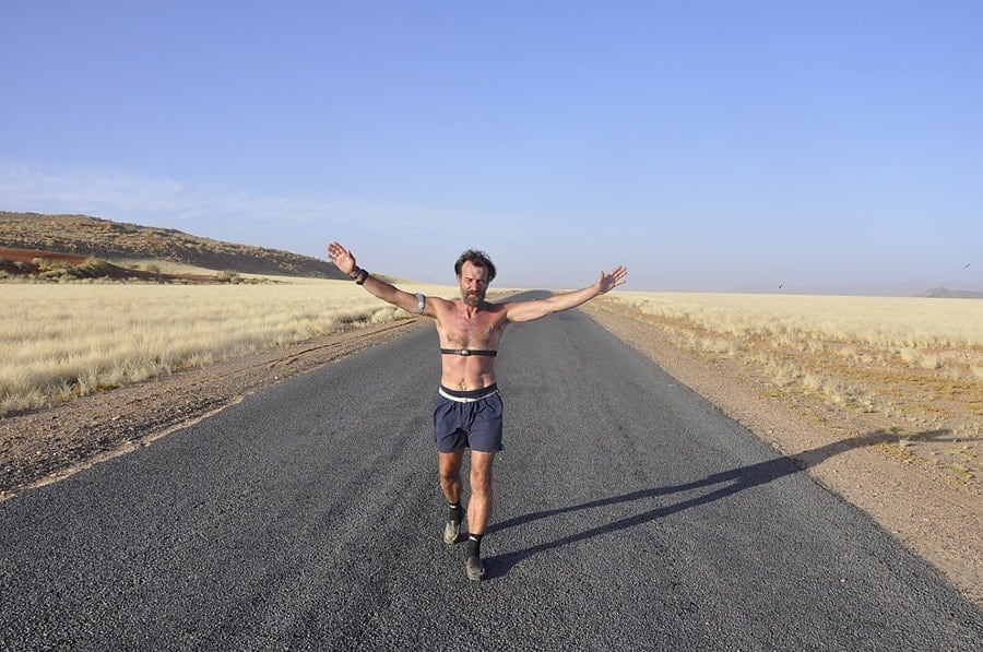 Wim Hof walking on a road in the Namib desert.