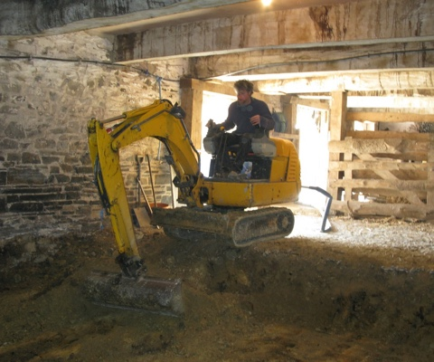carefully digging out the small space underneath the old stables