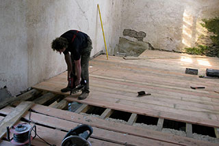 Fitting a new wooden floor during barn restoration