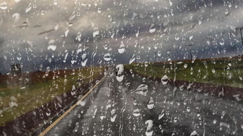A country road, seen through a rain covered windscreen