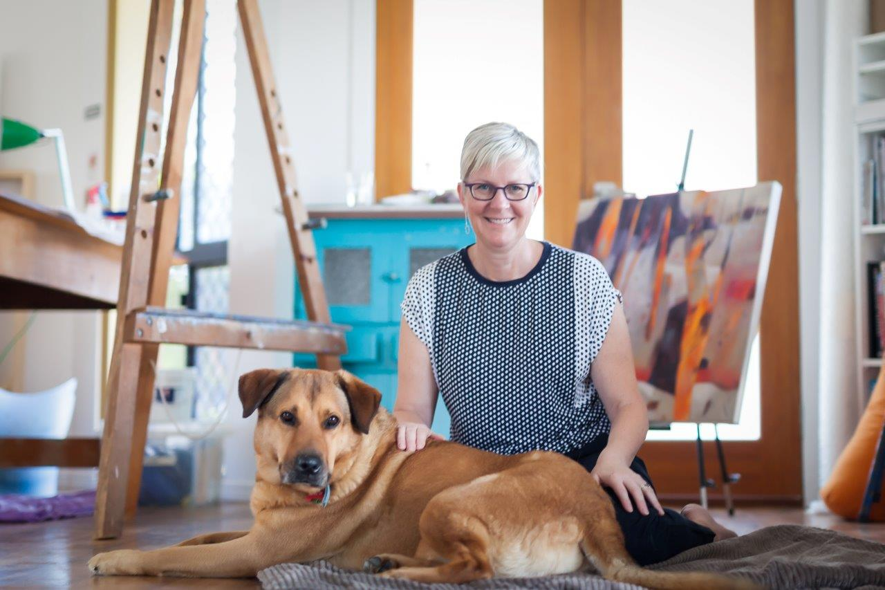 Adrienne and her dog Sunday sittin gon the floor of her art studio