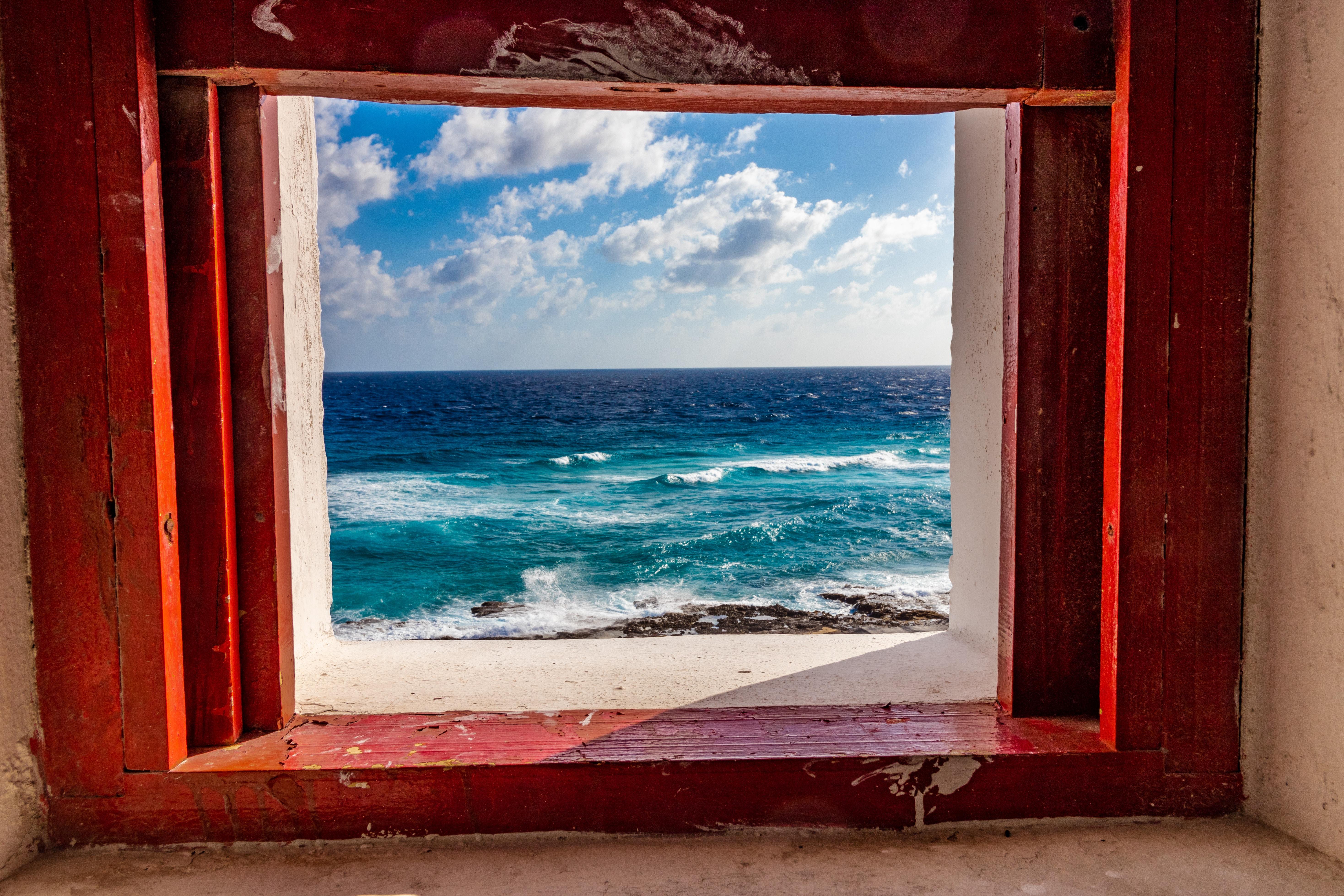 view of the blue ocean through a window