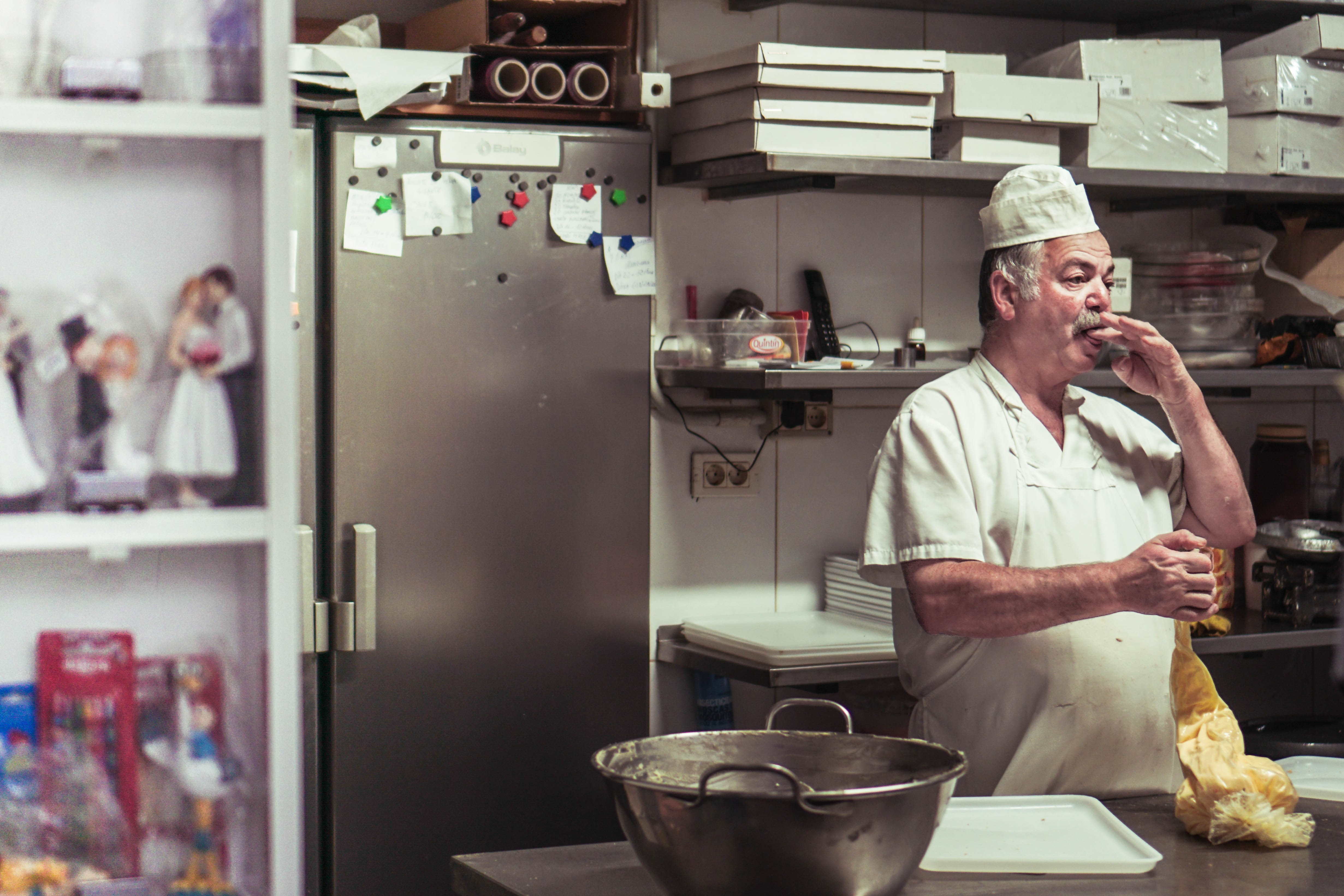 gray-haired chef with mustache in a bakery kitchen