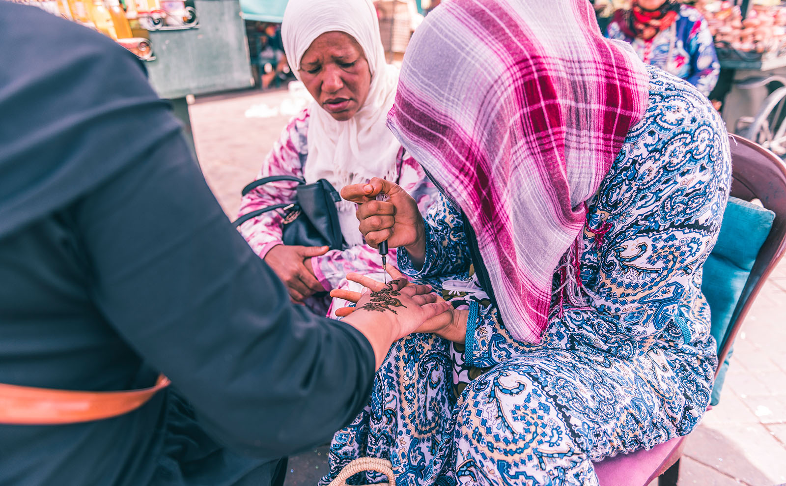 moroccan artist drawing a henna tattoo on a hand