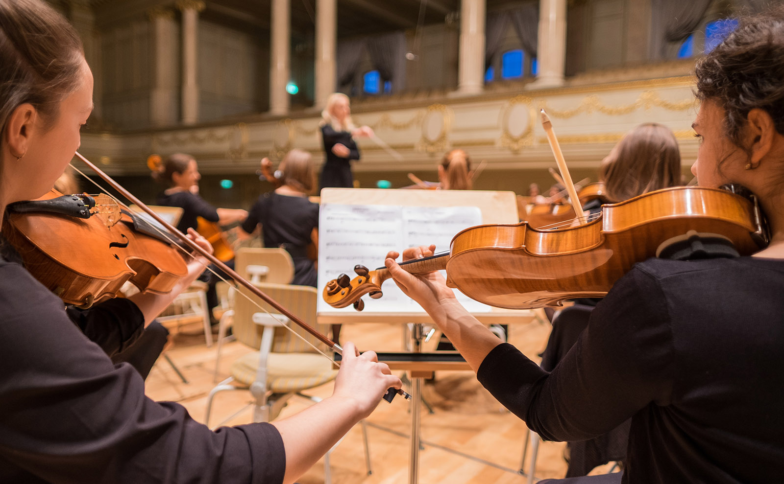 young people playing the violin in an orchestra