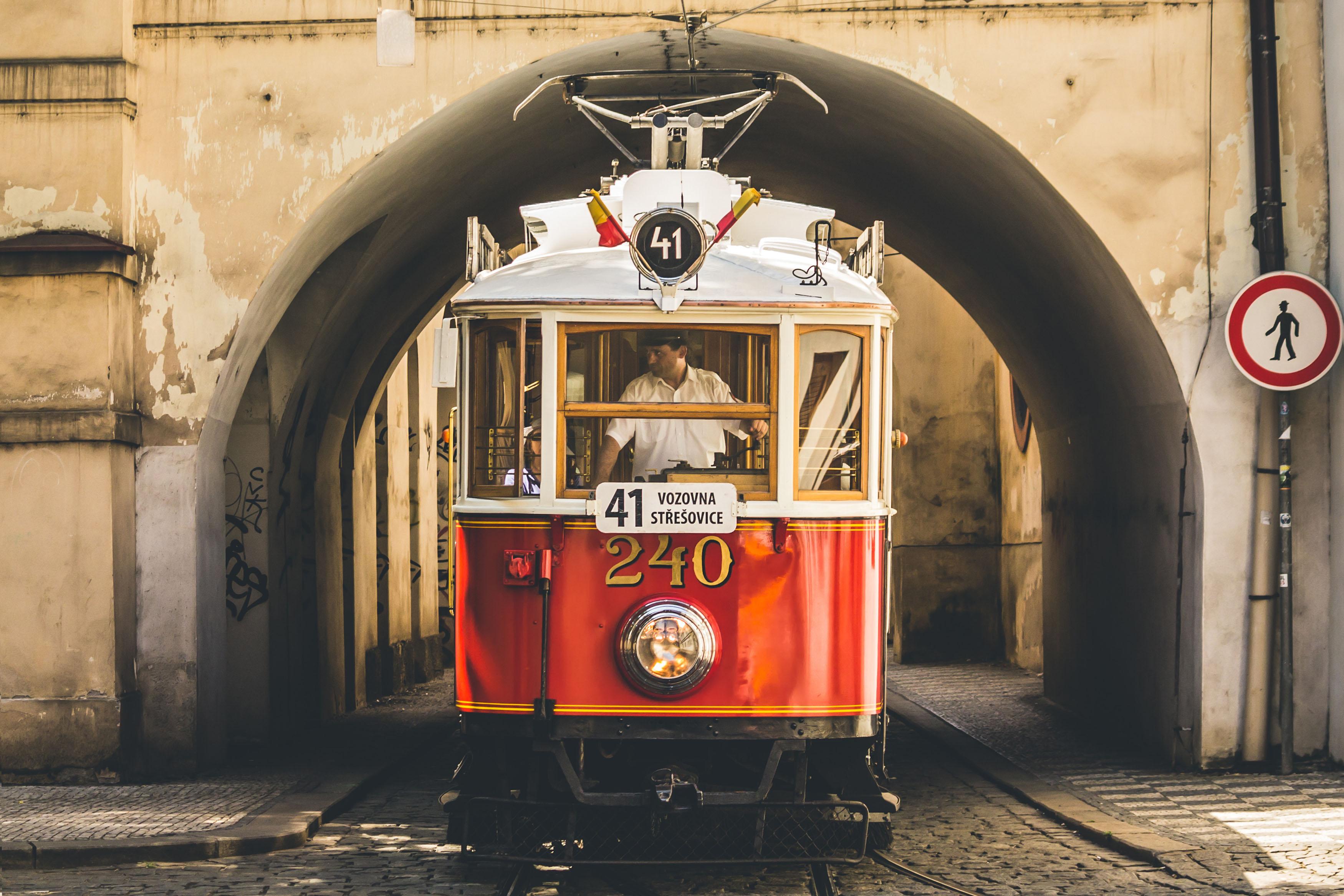 tram pulling through an arch in prague