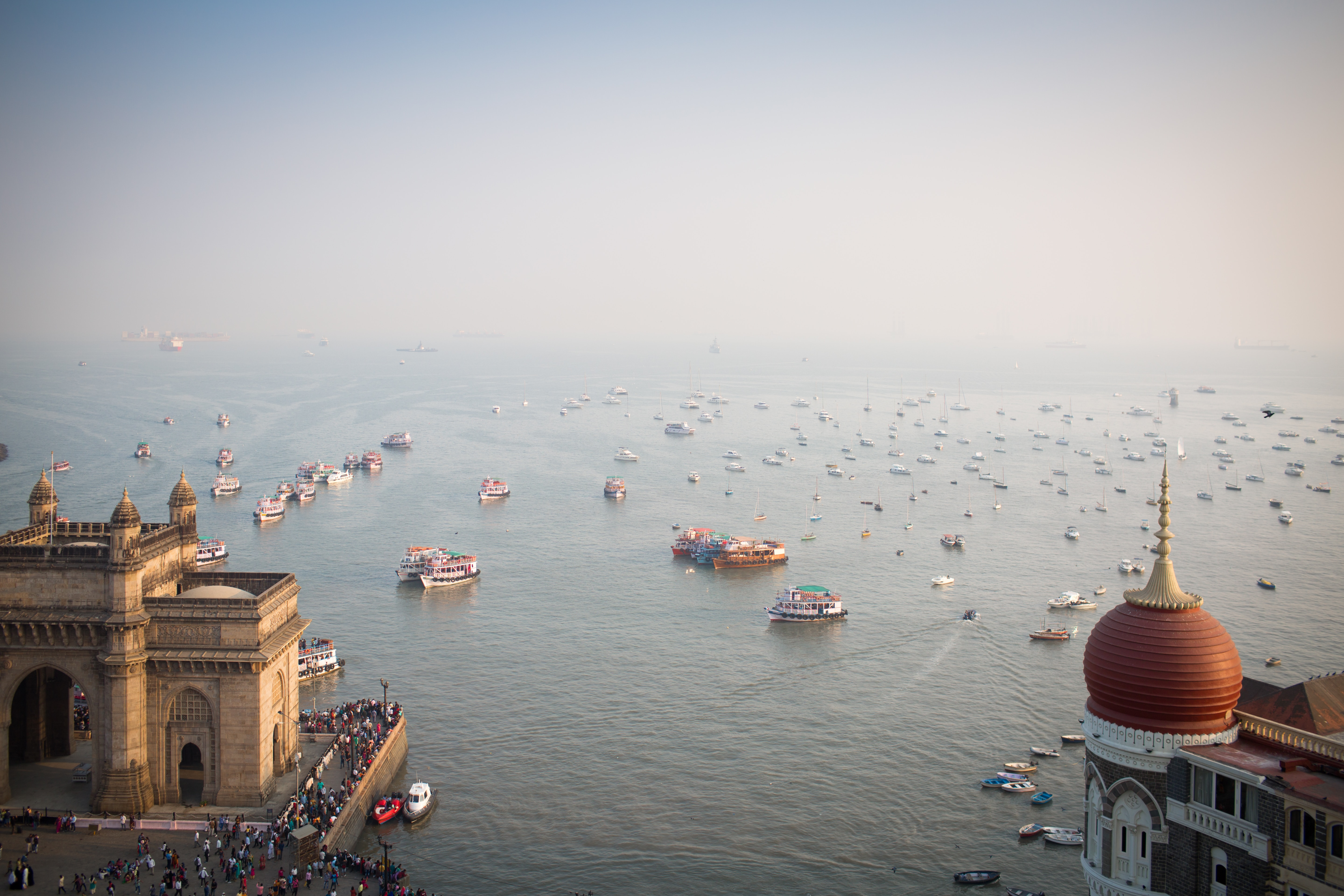 boats on the water in front of the gateway of india in mumbai