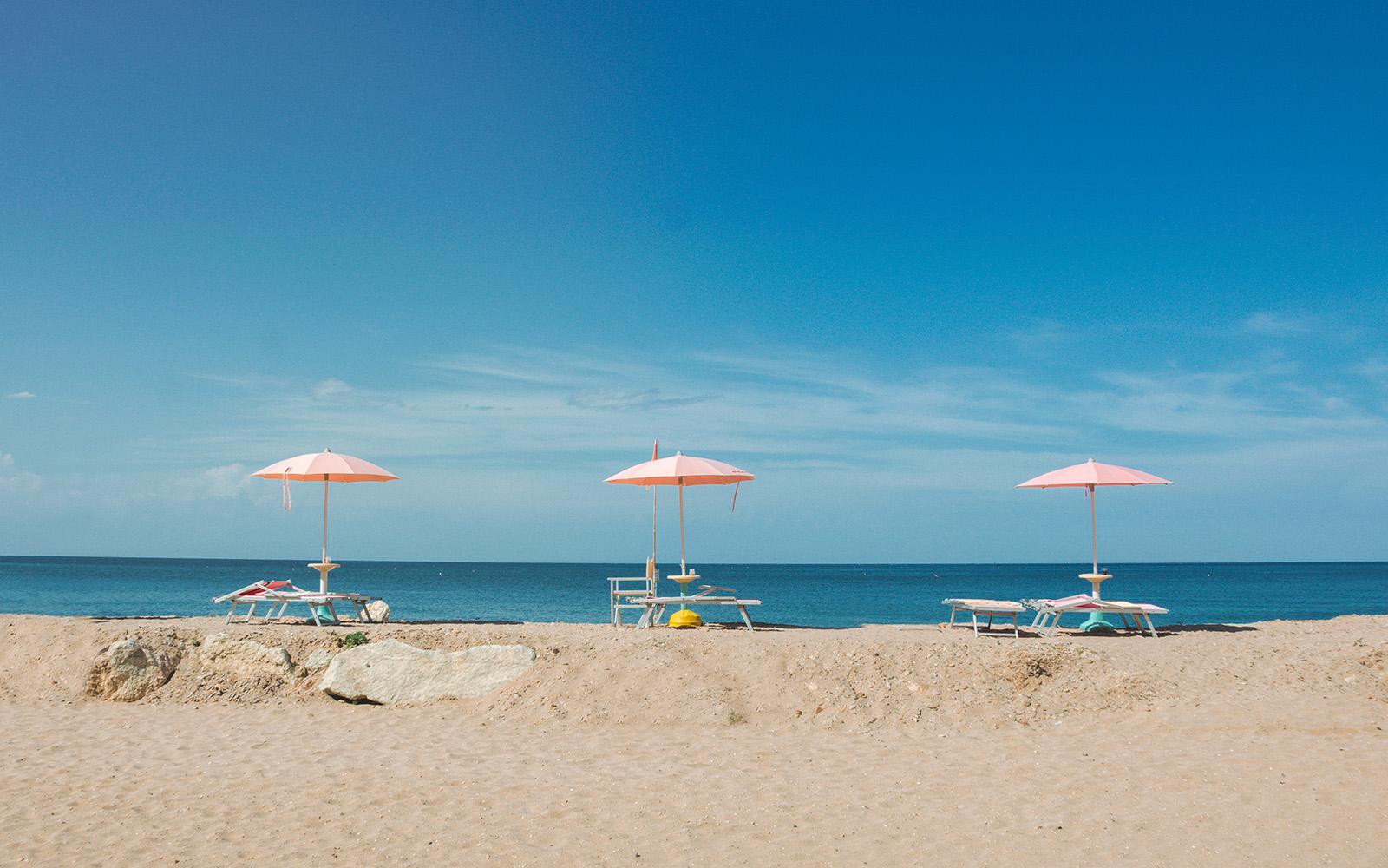 three pink sun umbrellas lined up on the beach