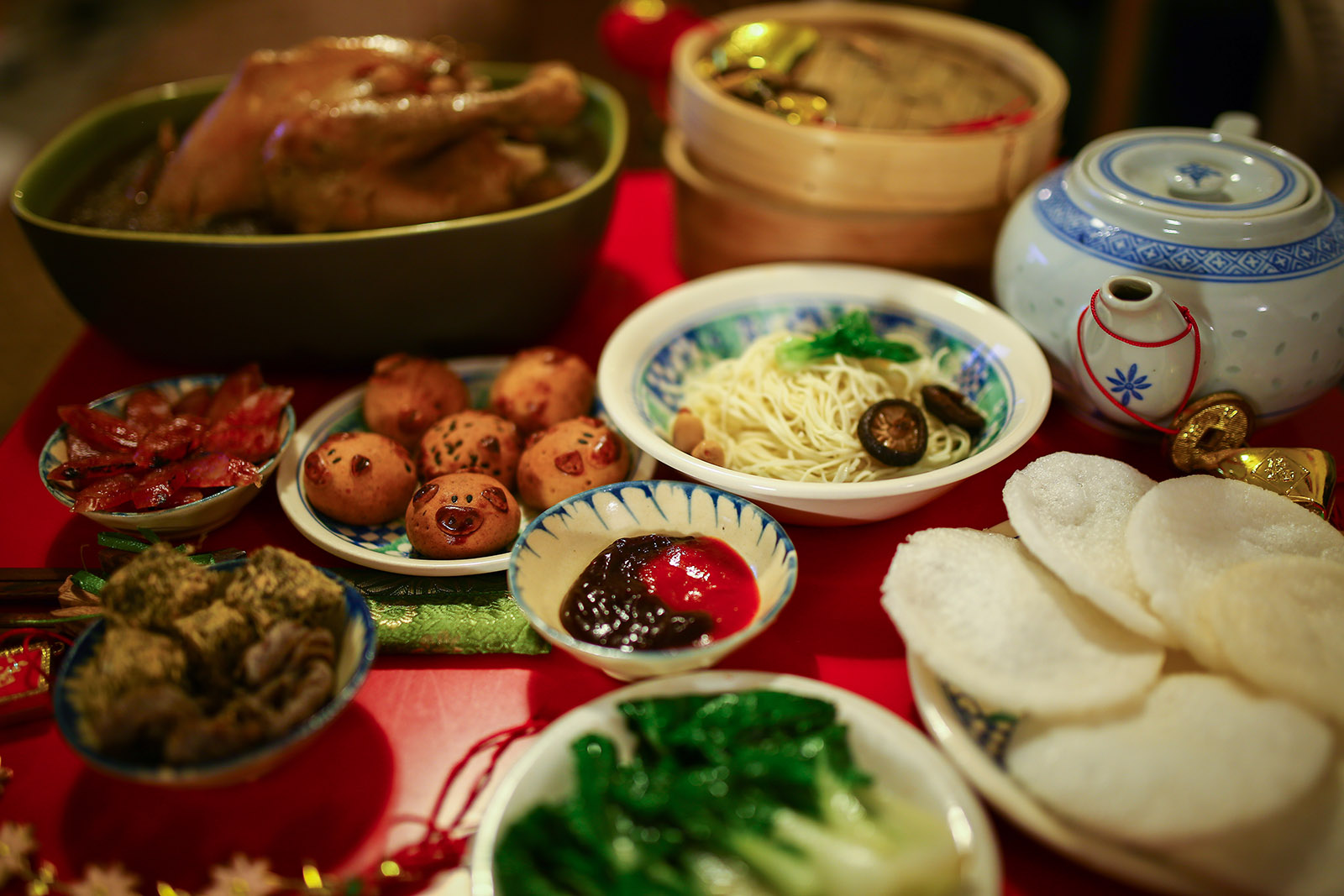 dishes of colorful chinese food on a wooden table
