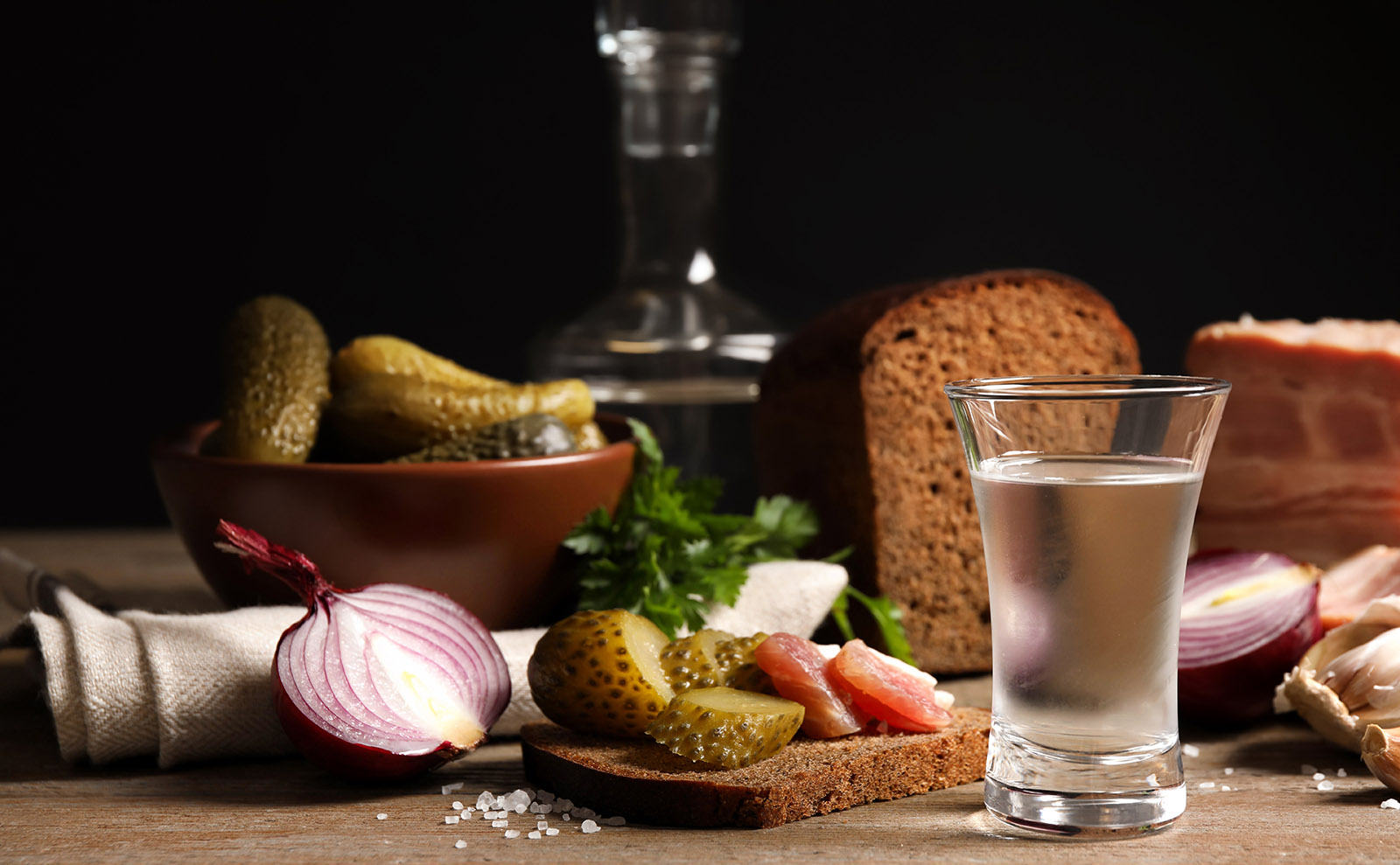 wooden table set with vodka, brown bread, meat, and pickles