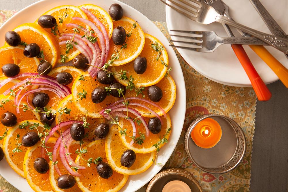 orange slices and black olives arranged on a plate
