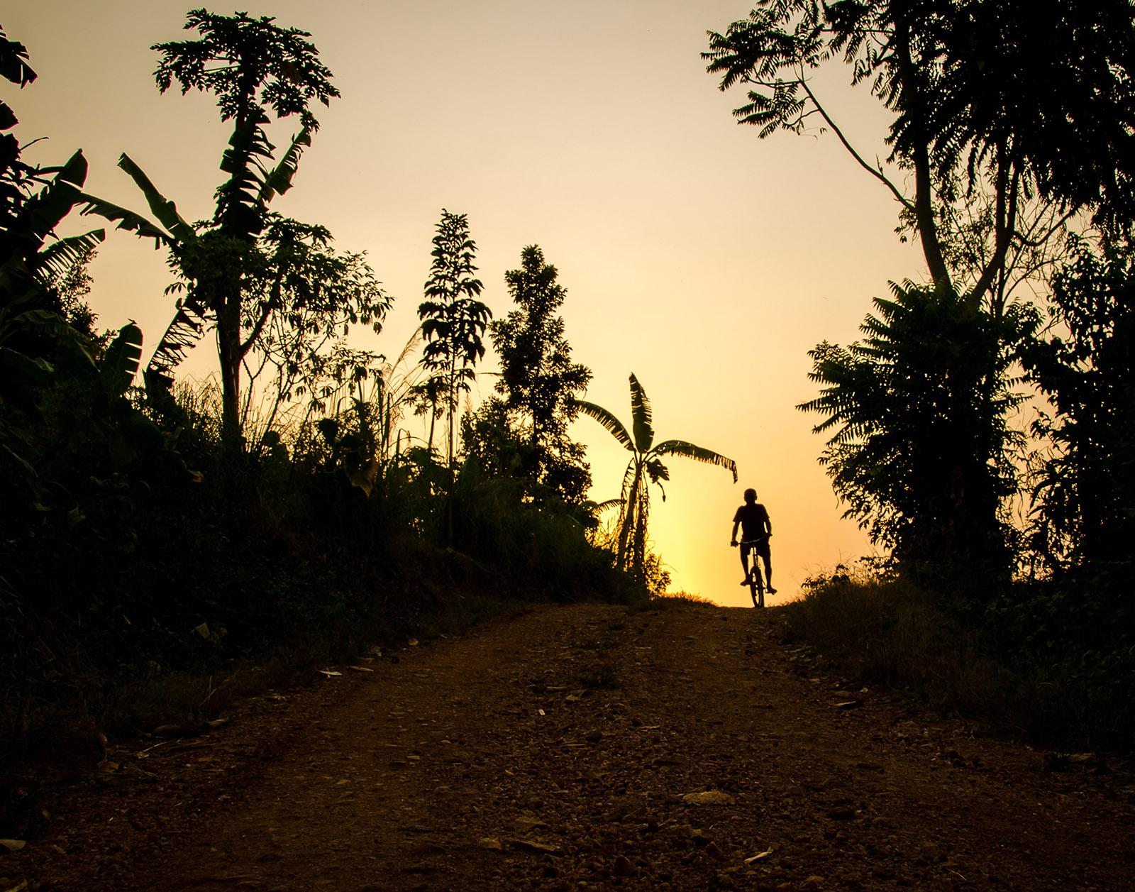 a boy rides his bike at sunset in uganda