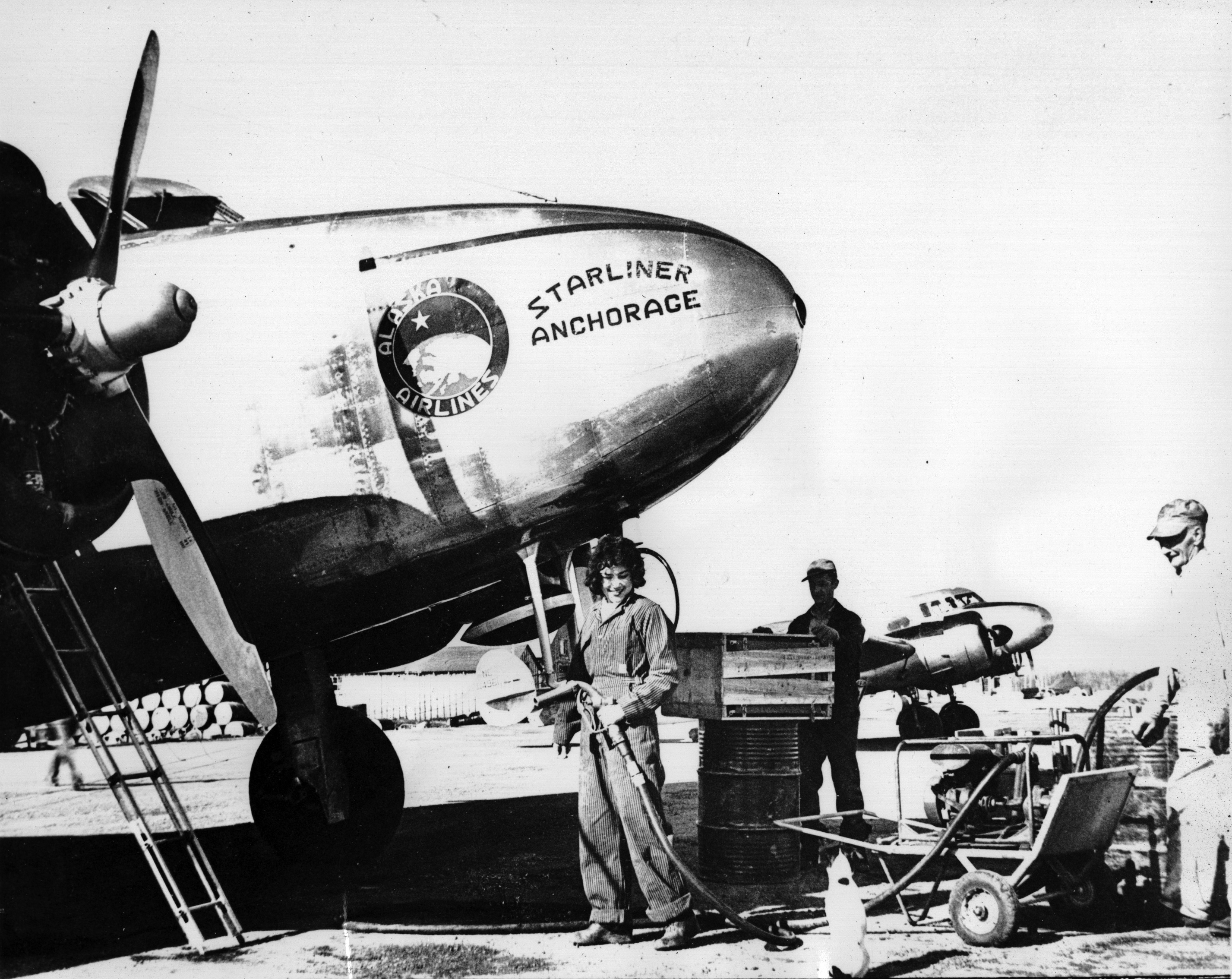 black and white photo of a young woman fueling a vintage airplane